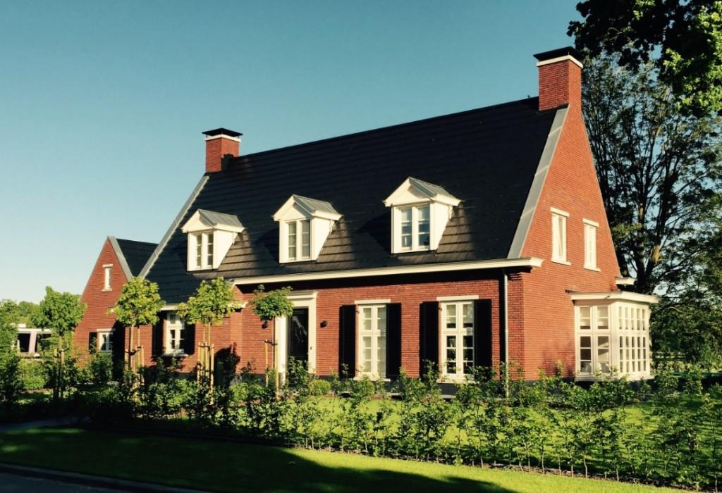 Vrijstaande-woning-met-verspringende-gootlijn-rode-baksteen-schoorstenen-en-donkere-vlakke-dakpannen-1024x700
